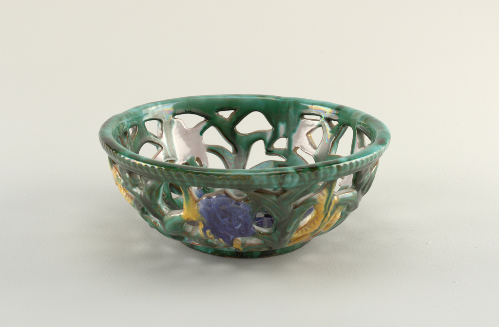 Round bowl pierced into a leafy floral pattern. Thick green glaze with lustre.