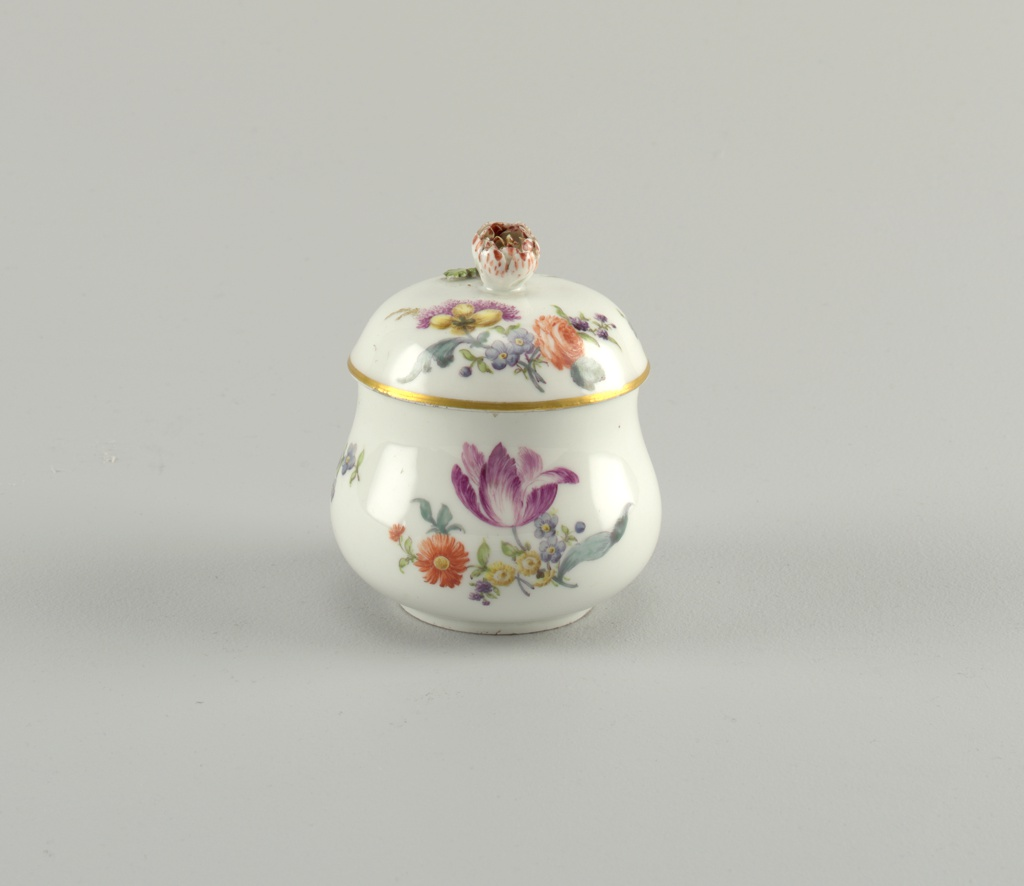 Sugar bowl and cover part of a personal traveling tea-set. white porcelain with floral sprays and cover with flower handle.