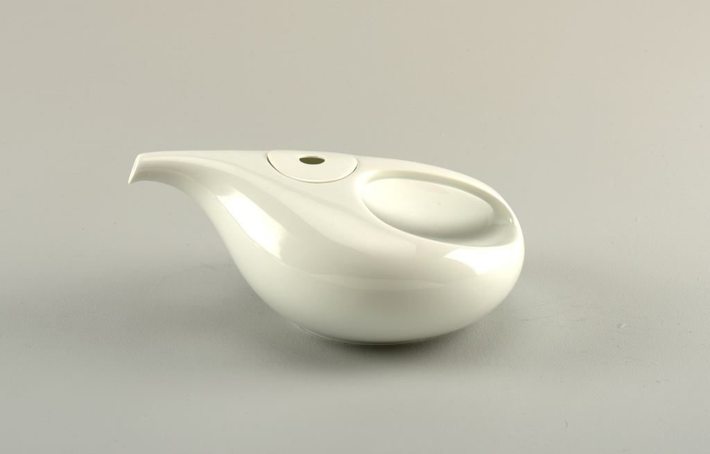 White body of angled, elongated ovoid shape; spout and handle whole with the piece; small circular lid with circular depression in center, inset between handle and spout.