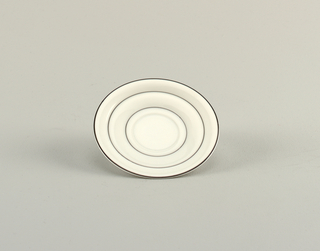 White porcelain saucer decorated with black concentric circles.
