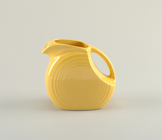 Yellow disc-shaped pitcher with series of concentric circles molded at edges; mouth angled back, transitioning into curved handle; small circular spout.