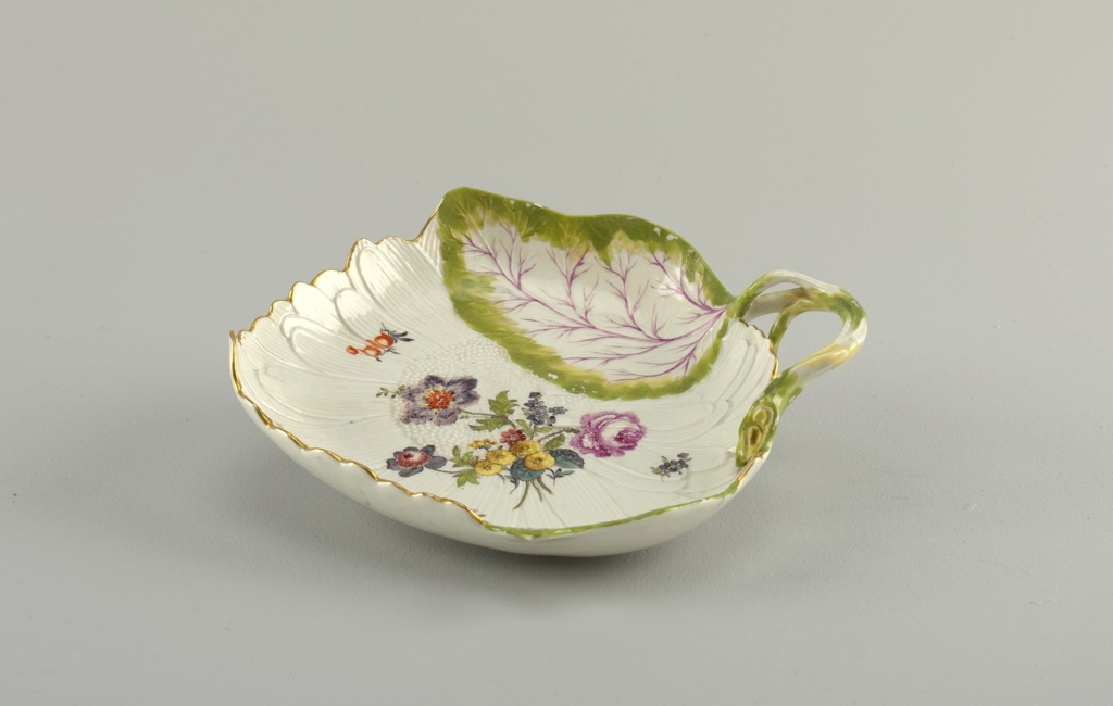 Modeled in the shape of an open sunflower and two leaves, with stem forming handle. Overglaze, polychrome bouquet and scattered flowers. Leaves edged green and vein purple. Gold rim.