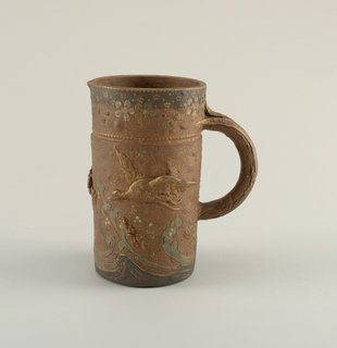 A brown colored pitcher with a very small spout and a handle. The piece is decorated with outdoor scene depicting water and birds flying above along with some flower detail around the top.