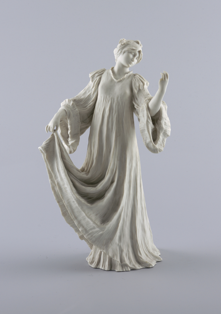Figure in long, flowing gown, full sleeves. Head thrown back, facing upraised left hand. Right hand holds edge of skirt.