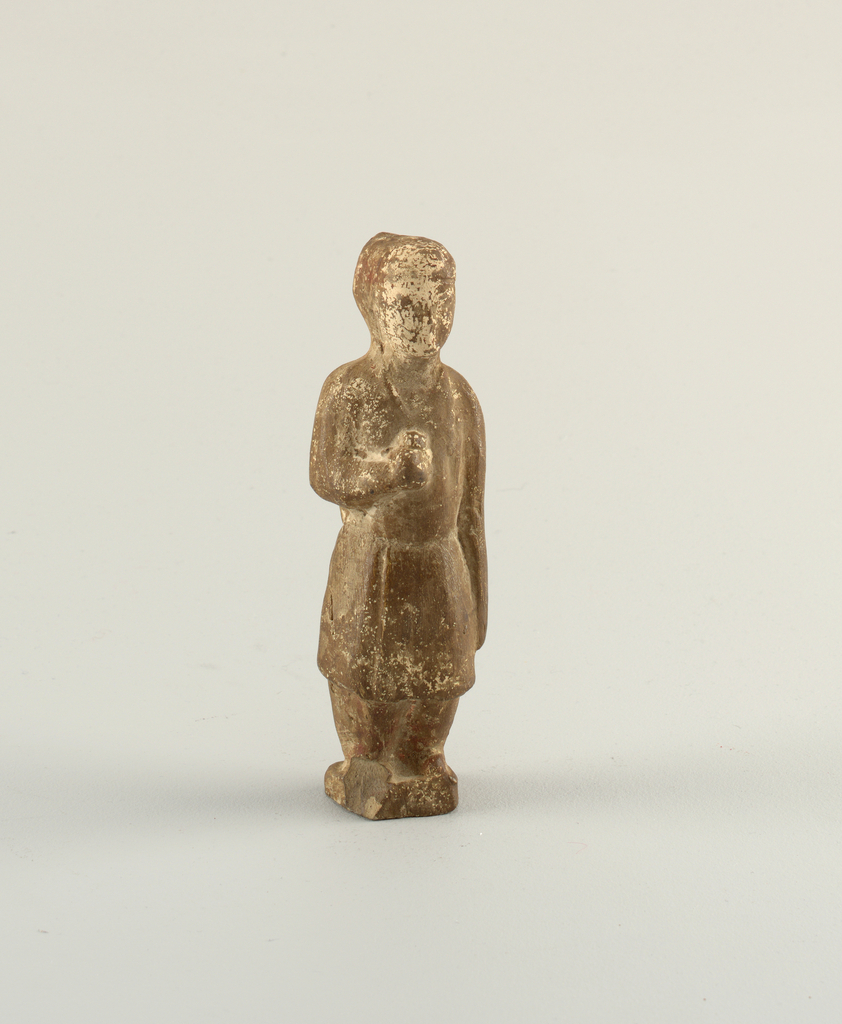 Male figure with knee-length coat, holding round object in lifted right hand. Hair arranged in elongated shape on back of head. Square plinth, chipped. Figure made in two-piece mold.