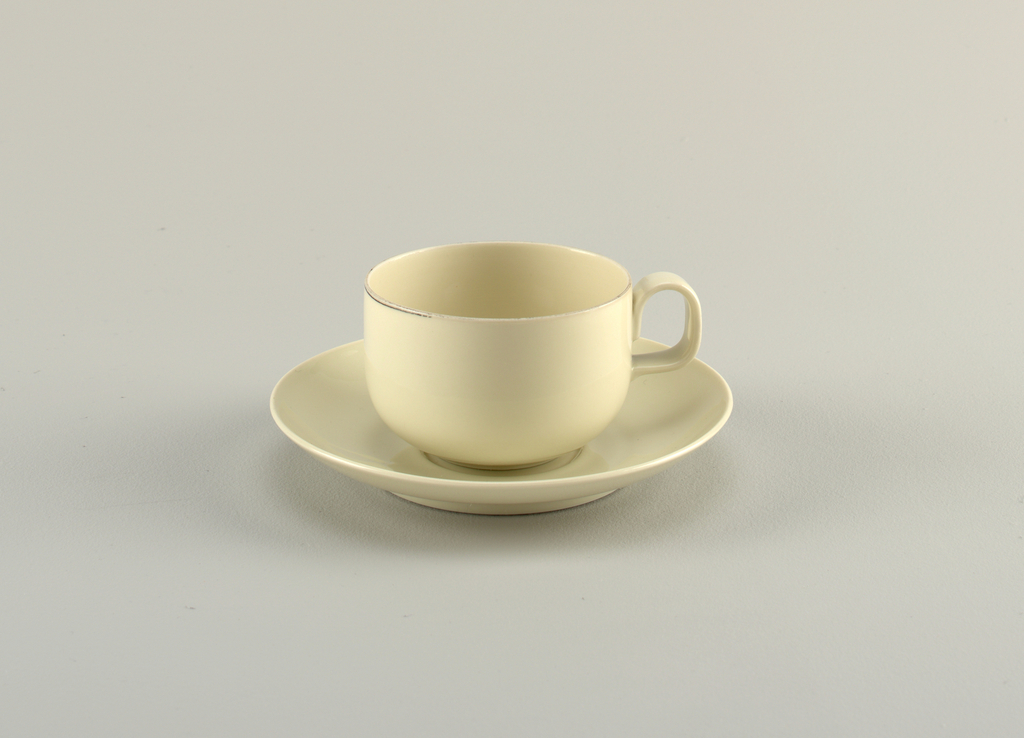 """Creamy-grey porcelain body. (a) cup is cylindrical in shape, with curved lower section that tapers to circular foot. Handle is placed high on body, formed as reversed """"U."""" Platinum band painted around lip. (b) Saucer plain. Circular, with upward curve at rim and central circular depression."""