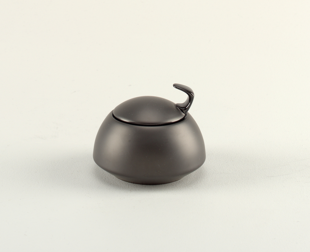 Black circular bowl, flat base with flush lid and attached to lid a hook-like knob that is glazed.