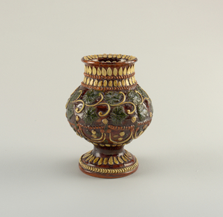 Bulbous footed vase decorated in yellow, green, and brown relief, with pattern of leaves and C-curves.