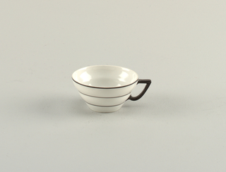White porcelain cup with flared mouth; decorated with thin black bands circling the body; black handle.