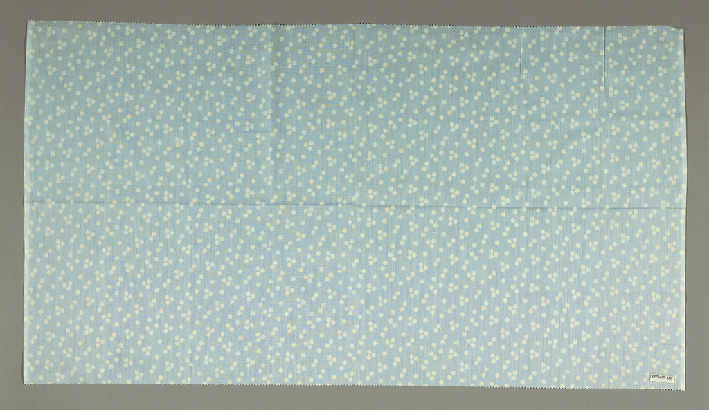 Length of light blue cotton patterned by scattered clusters of white circles with crenellated edges.