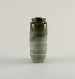 Sea green vase. White clay body, thrown. Cylindrical body with short inset neck with thick lip; molded flat foot. Decorated with two fish above three tiers of foamy waves. Underglaze slip colors are shades of green: fish are an olive green, water is blue-green with slightly raised ridges of white. Above fish is dark olive green area. Allover light green glaze; fine cracklature. Interior and bottom glazed.