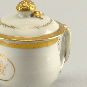 Porcelain cup and cover with a decorated handle and gilt initials belonging to a serving set.