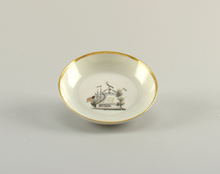 A white cup and saucer with a gilt lined rim on both. Each have a painted ship in black with gilt initials on the sails.