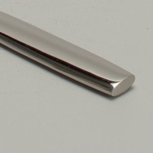 Mirror surface stainless steel. Blade and handle integral; straight blade with curved, tapered point; twisted at juncture of handle and blade. Handle flattened, oval in section with blunt end.