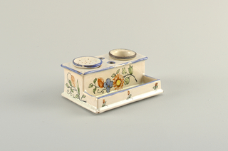 Earthenware box with two cups for ink at top and shelf at bottom; decorated with orange and blue flowers on white background.
