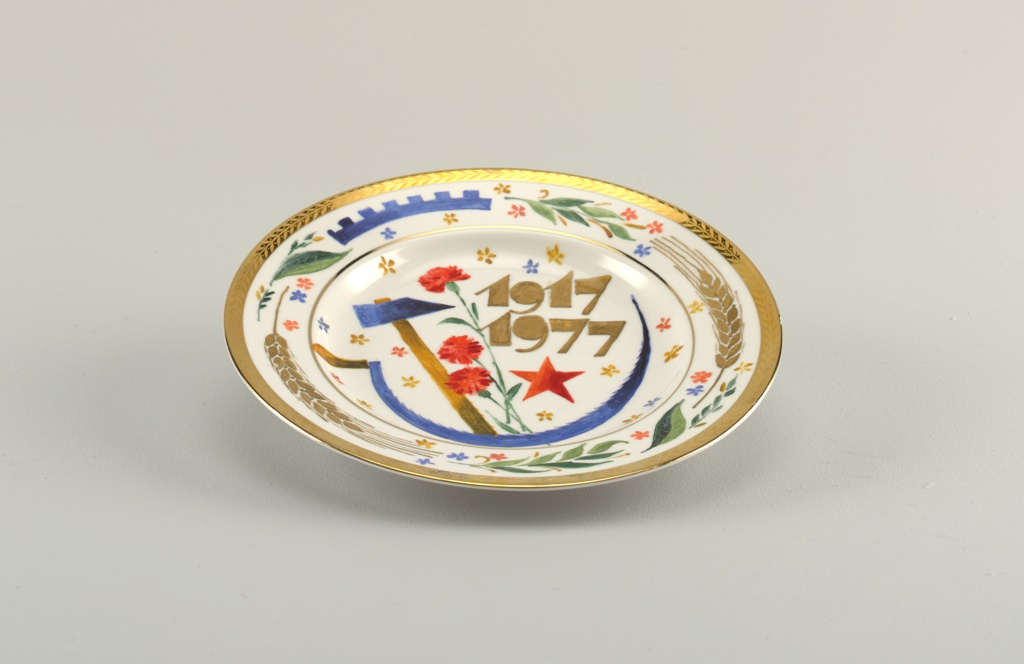 "Circular; in the center a hammer, sickle, red star, red carnations, stylized flowers and the inscription ""1917-1977;"" around the border a gilded rim with leaf motif, and wheat stalks, section of cog wheel, stylized flowers and leaves"