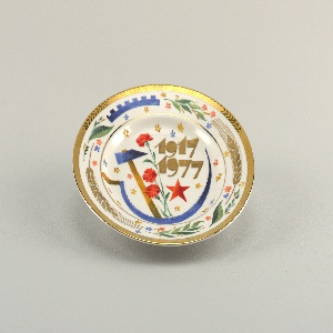 """Circular; in the center a hammer, sickle, red star, red carnations, stylized flowers and the inscription """"1917-1977;"""" around the border a gilded rim with leaf motif, and wheat stalks, section of cog wheel, stylized flowers and leaves"""