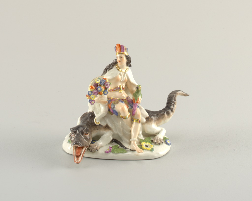 Female figure with feather skirt, mantle and headdress, holding cornucopia and parrot, seated on an alligator facing left.