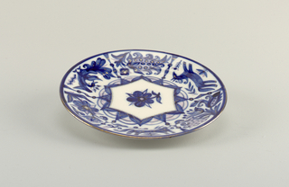 Circular; painted in blue, with some gilding, in the center a stylized flower in reserve, around the border six panels alternating with stylized animals and flowers