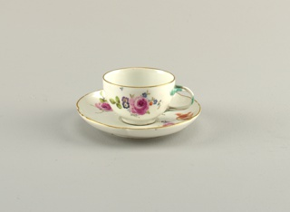 Cup and saucer part of a personal traveling tea-set.  in box. Cup has double-curved side, cylindrical foot, intertwined twig handle touched with green. Saucer flat, with steeply-curved side and gilded edge. Cup and saucer decorated with scattered flowers and floral sprays.