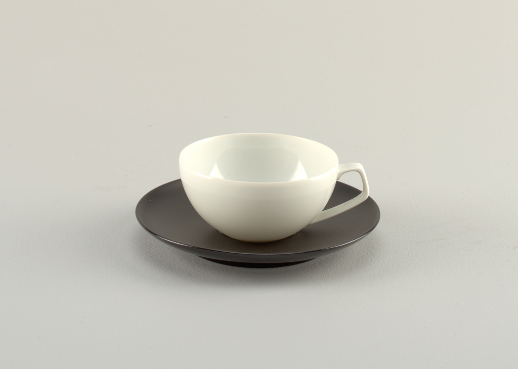 Open white cup with angular handle on a black porcelain saucer.