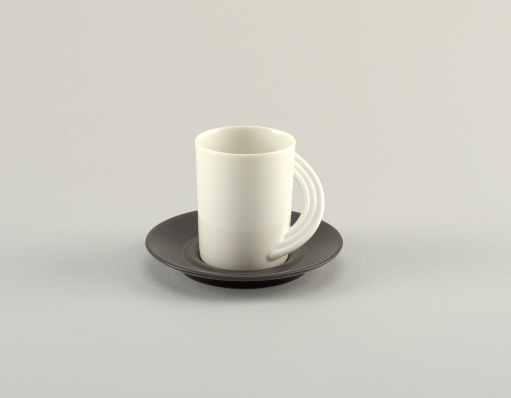 White cup with straight sides and curved handle that reaches around half of cup, made of three semi-circular tubes, on a black saucer.