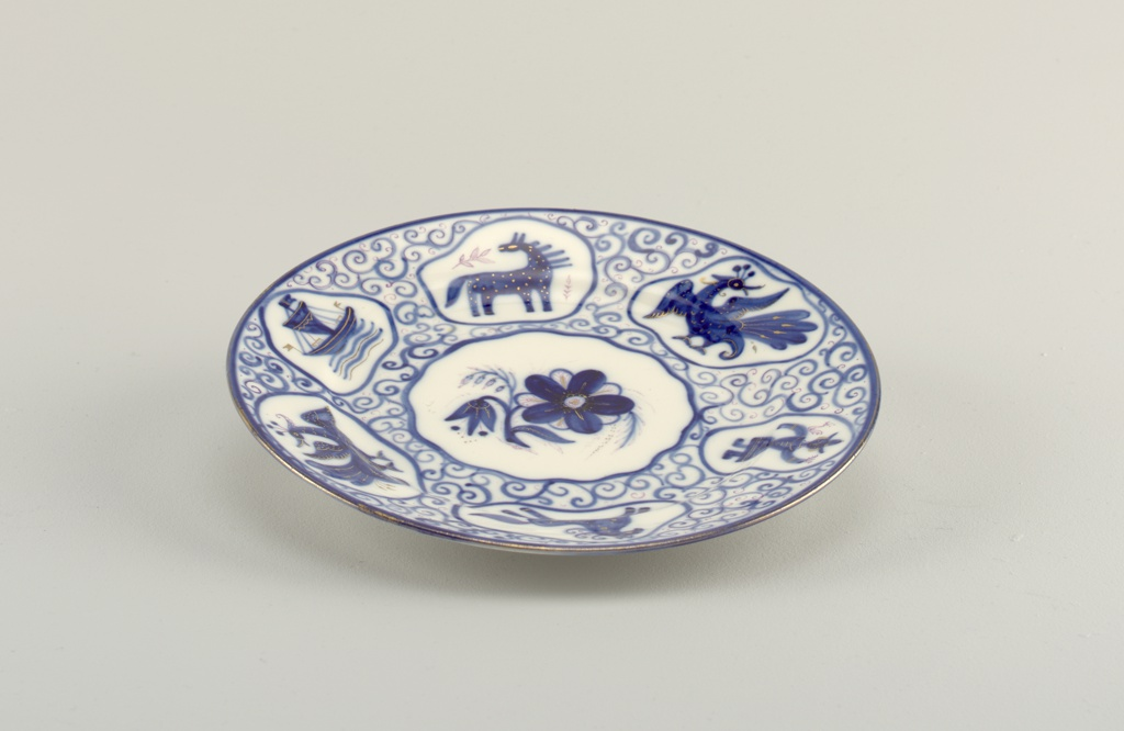 Circular; painted in blue with some gilding; in the center a reserve with flower; around the border six reserves with stylized animals, a man, and a ship; scroll pattern in background