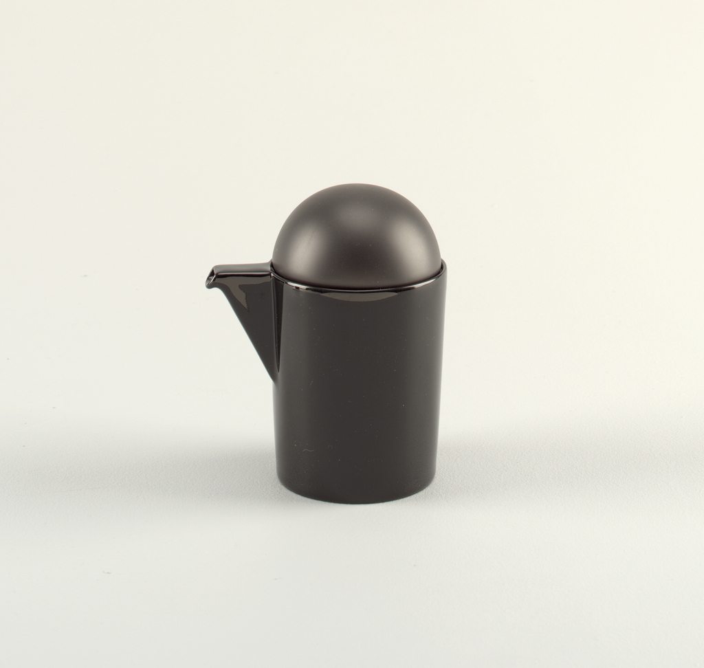 Black pitcher with angular spout and bowl-shaped lid.