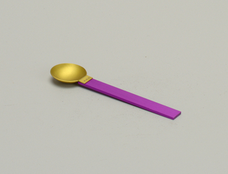 Flat rectangular aluminum handle with brushed surface, adonized purple. Round bowl adonized gold and affixed to handle side with three silver rivets.