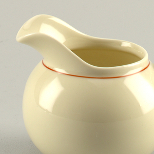 Molded creamy-grey porcelain body. Spherical body with circular foot ring and flared curved lip at front. Simple loop handle. Red line around neck and in middle of handle on both sides.