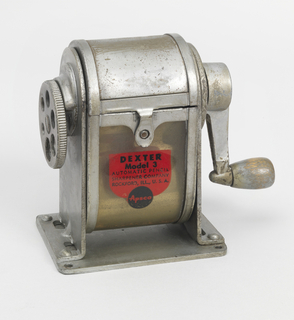 Upright roughly rectangular metal container, curved at top and bottom; celulose cover over lower section, with red and black logo showing model name and company name and location; gear-like circular pencil holder on left side, crank on right side; flat, square base with small hole at each corner.