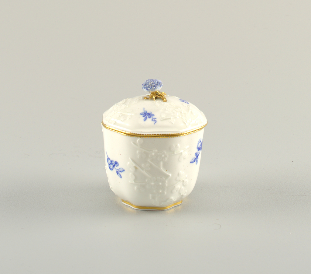 Hexagonal form with rounded corners. Molded with relief decoration of Japanese-style flowers on body and lid. Scattered sprays of blue flowers. Gilding at edges and on the stem of the floral finial, whose petals are painted blue.