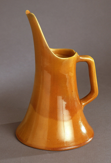 Cylindrical body flaring to circular foot; circular mouth with rising, elongated spout; squared, angled loop handle. Overall yellow-brown glaze, mottled and finely crackled.
