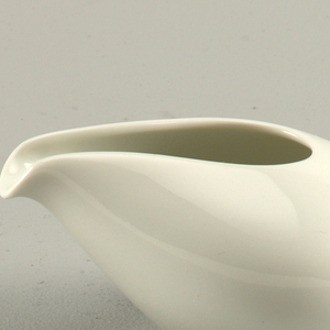 White porcelain creamer with an altered egg or seashell form. Creamer is to be hand held with its natural spout.