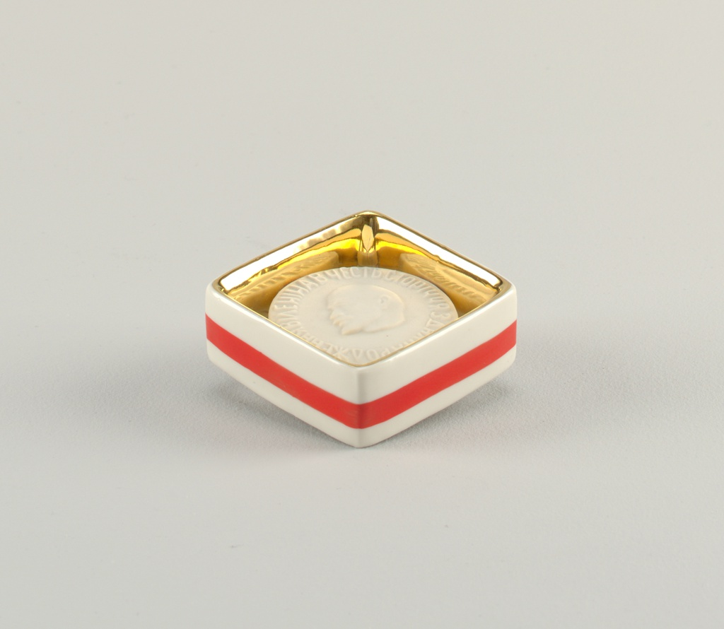"""Circular disk of bisque porcelain with bust of lenin in relief and inscription (in Ukranian?) """"In honor of the 100th anniversary of the birth of Lenin;"""" enclosed in square frame with red enameled and gilded trim"""
