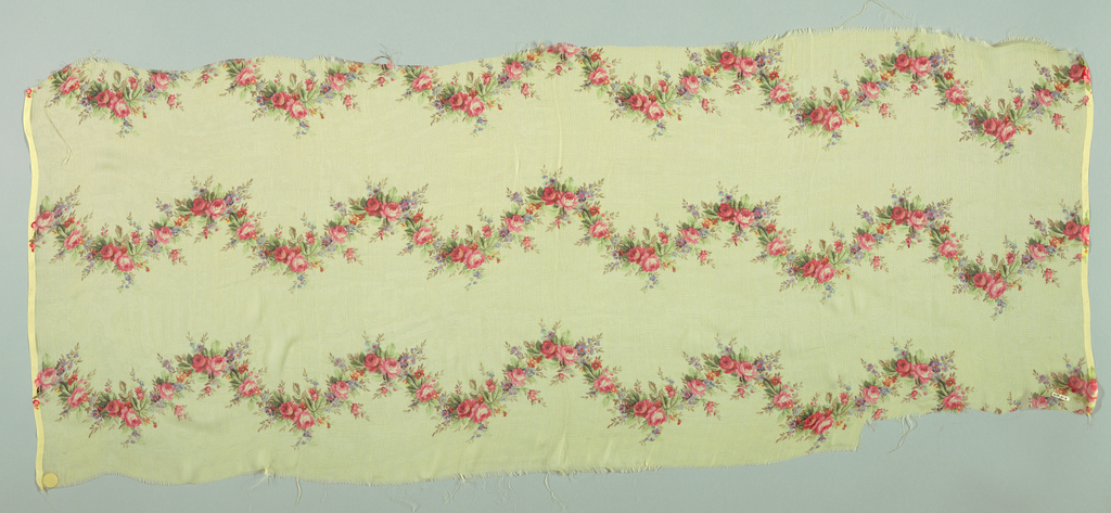 Pale yellow ground with horizontal garlands of small-scale roses and other florwers. Both selvedges present.