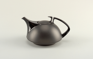 Black hemispherical body with tapering spout and squared strap handle opposite; slightly domed lid with curved tab-like handle at back.