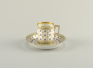 A porcelain cup and saucer with floral pattern in gilding.