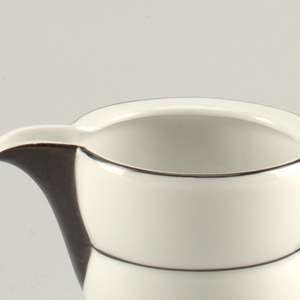 White porcelain creamer with thin black bands circling the body; black handle and spout.