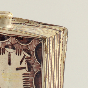 """Book-shaped flask with short circular neck and mouth at top, near """"spine""""; the whole decorated in brown glaze on a white ground, depicting book elements: front """"cover"""" decorated with brown floral and tassel motif; """"spine"""" with horizontal bands of brown and white; the top with brown lines denoting """"pages."""""""