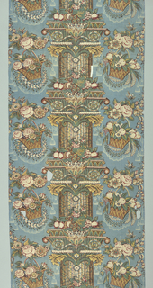 Pillar print showing a central fluted column banded by elaborate capitals and festooned with garlands of flowers and fruit on a blue ground. On either side is an alternating pattern of flower garlands and large baskets of flowers and fruit. The bold composition is complemented by a delicate pattern of tassels and lace swags in the background.