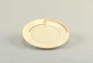 Round white plate with flat marli. Light orange line of glaze at rim and partial circle of bright orange glaze within.