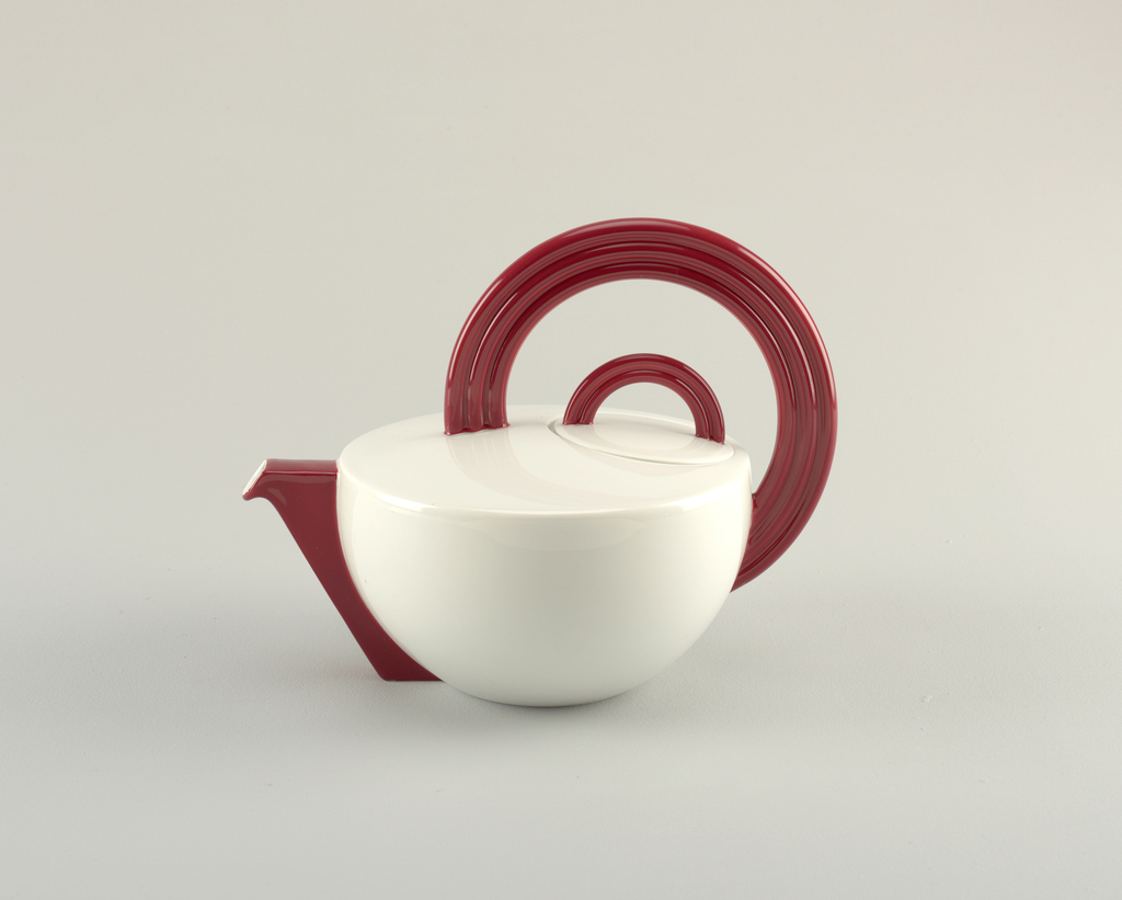 Deep bowl-shaped white teapot with flattened top and flush lid; with blood red angular spout, handle and knob. Handle composed of three concentric tube-like components in a large ¾ circles and knob of two concentric tubes in semi-circle.