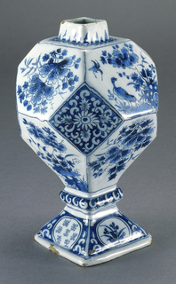Twelve-faceted body with short square-sided neck on a 4-sided domed foot with knop; painted in underglaze blue on white with chinoiserie designs of flowers and birds, leaves, pseudo-Chinese characters in reserve on base.