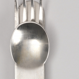 Straight-sided, four tined fork; integral handle with concave indentation and curved terminal.