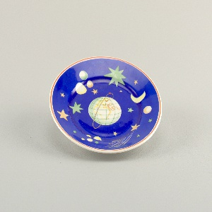 Circular form; decorated with earth, stars, moon, and planets against a dark blue background; orbiting around the earth, a small red sphere (Sputnik); thin gilded band around outer edge.