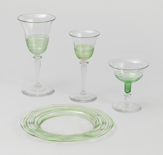 Clear glass, circular base, tall baluster-shaped stem, bowl with sides flaring out towards rim. Light green threading applied to outside of lowersection of bowl.