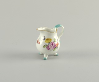 Pear-shaped with simple lip, looped handle and three curving feet. Decoration of scattered sprays of flowers; gilding about shaped edge' touches of teal on handle and feet.
