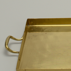 Rectangular, flat bottom; edges bent at right angles to form gallery; each corner secured with brass rivet. Curved tapered handles at both long ends; attached to tray with six rivets. Undecorated.
