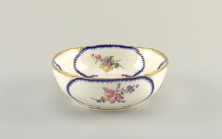 Oval bowl on low foot.  Floral bouquets within oval cartouches outlined in gilding and cobalt. Gilding at rim and foot.